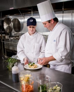 Photo of culinary school chef and student in commercial kitchen. Industrial photography by Nashua, NH commercial photographer Dan Splaine.  Corporate assignment photography for public relations, marketing and advertising clients in New Hampshire, New England  and nationally. For more information about our commercial photography services contact us at info@dansplainephoto.com  ©2012 Daniel J. Splaine – All Rights Reserved
