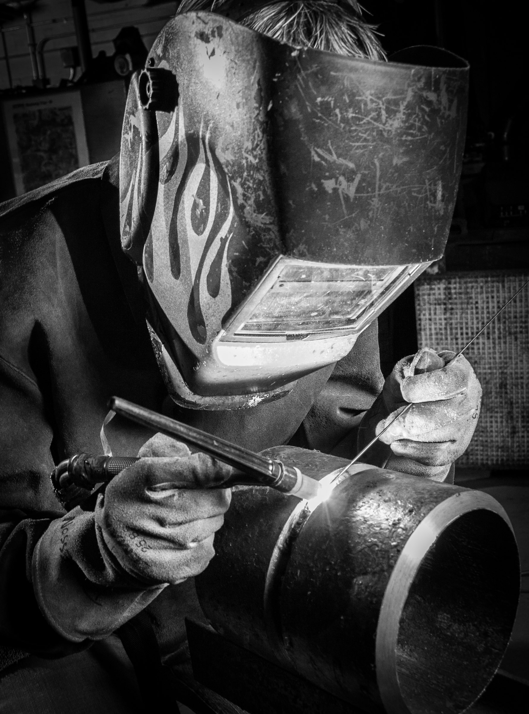 Black and white photo of a commercial welder working on pipe made at factory location